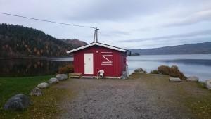 Liten rød bygning med Holsfjorden i bakgrunn