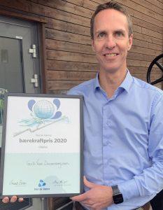 Bilde: Mann holder en diplom for Bærekraftprisen
