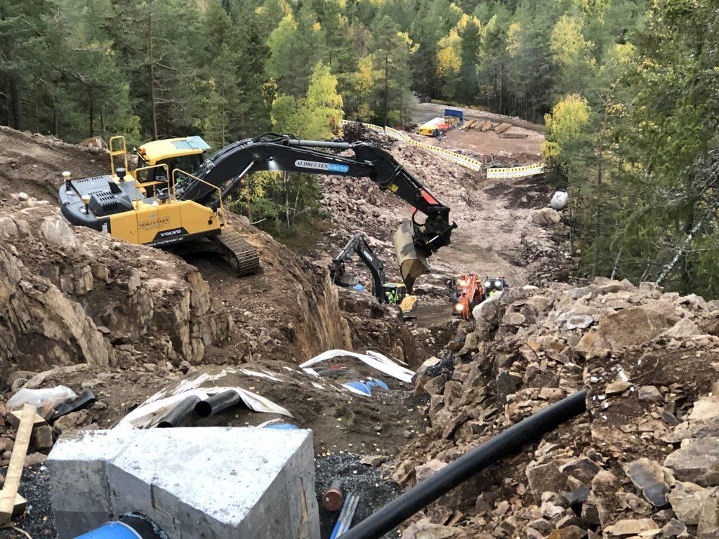 Bilde: Gravemaskin som står i bratt terreng og legger ned nye vannrør.