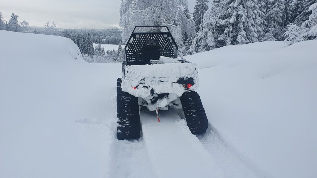 En ATV står på en ubrøytet skogsbilvei.