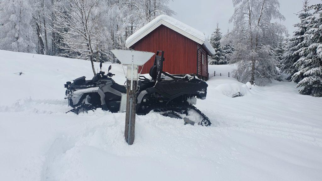 En ATV står i snøen ved en manuell nedbærsmåler.
