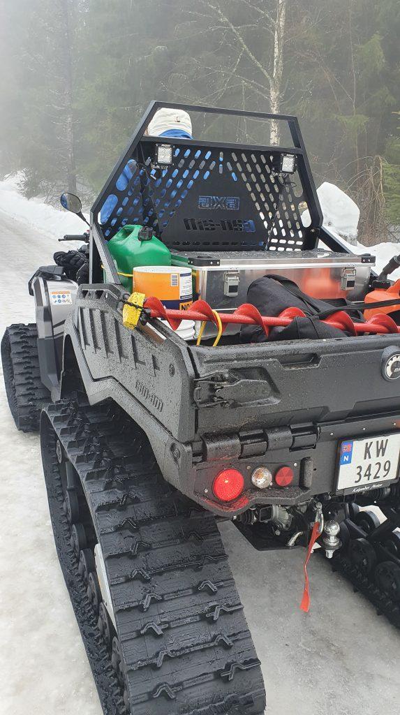 En ATV står på en skogsvei. I hengeren er det et isbor og annet utstyr.