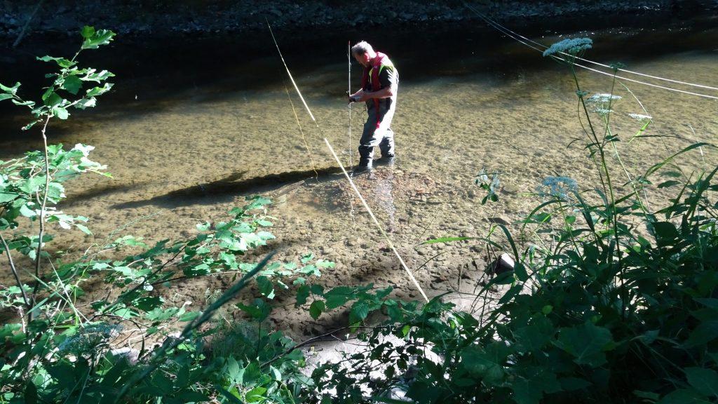 Bilde: Mann står ute i elven med målerinstrument