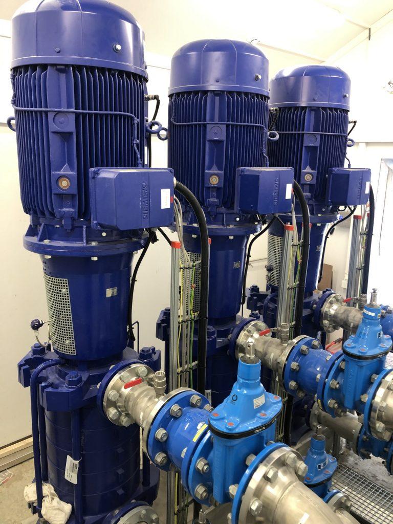Bilde: Tre blå nye vannpumper i et rom