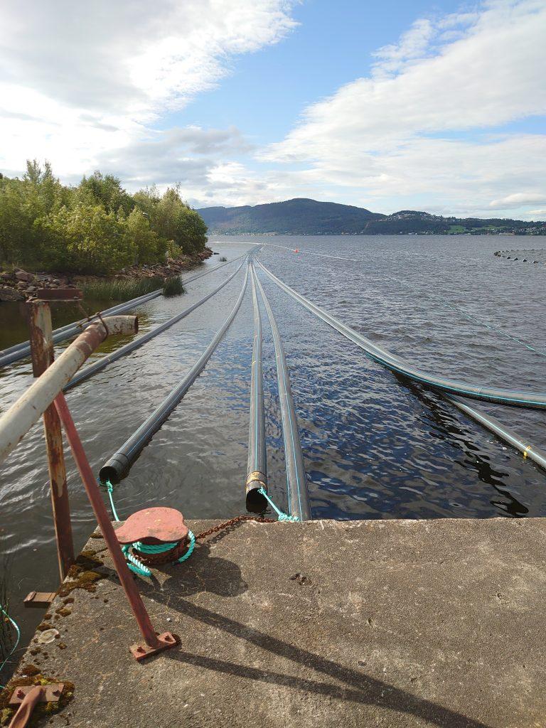 Bilde: store rør ligger fra en brygge utover i vannet