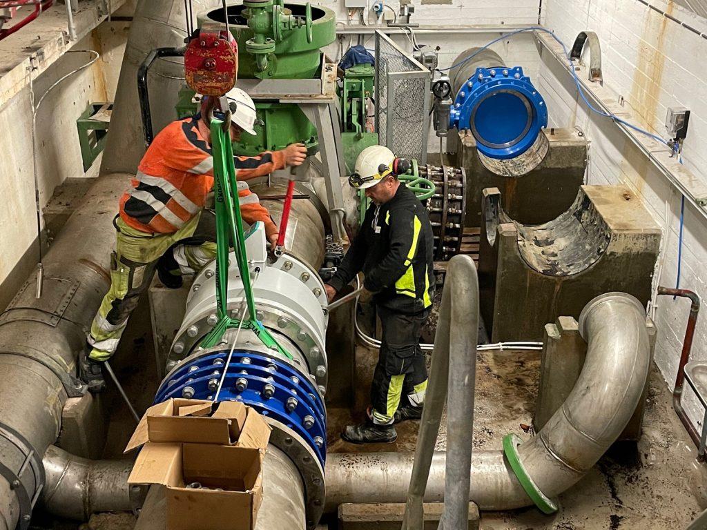 Bilde: To men jobber med å skru en rørdel inn på et stort vannrør.