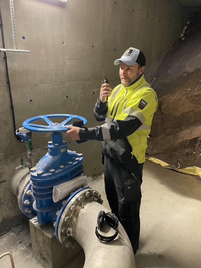 Bilde: en mann i arbeidsklær står klar til å vri på en ventil og har en nødradio telefon i andre hånden.